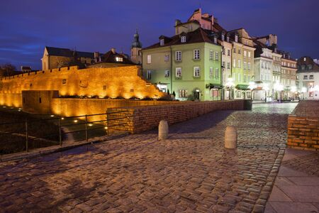 tenement: Warsaw Old Town skyline by night in Poland, fortified city wall, historic tenement houses
