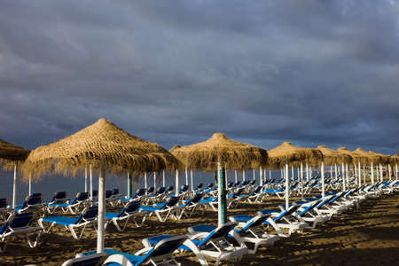 loungers: Sun loungers with umbrellas on a beach on stormy day