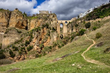 nuevo: Ronda rock, bridge (Puente Nuevo) and town in Spain, Andalucia landscape, meadow on a hill with footpath.
