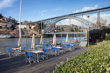 luis: Outdoor cafe tables on riverside boardwalk at Douro river and Dom Luis I Bridge in Porto and Gaia, Portugal Stock Photo