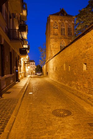 fortification: Medieval Old Town of Torun by night in Poland, cobbled, narrow street along city wall fortification, Dovecote Tower