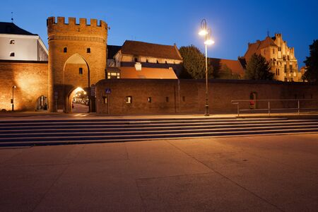 fortification: Torun, Poland, medieval Bridge Gate (Polish: Brama Mostowa) and city wall at night, Old Town fortification