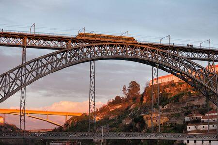 old metal: Dom Luis I Bridge with light rail metro line vehicle between Porto and Vila Nova de Gaia in Portugal at sunset Stock Photo