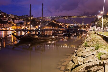 rabelo: City of Porto (Oporto) by night in Portugal, Dom Luiz I Bridge and traditional Portuguese Rabelo boats for wine barrels transport on Douro river, Gaia waterfront Stock Photo