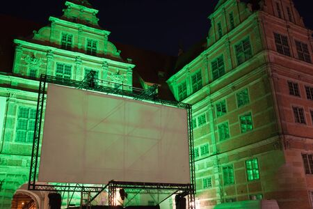 Large outdoor movie projector screen, empty display ready for projection at night, illuminated Green Gate, Old Town of Gdansk, Poland Stock Photo