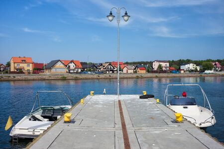 motorboats: Kuznica resort town on Hel Peninsula in Poland, pier with motorboats at Baltic Sea bay Stock Photo