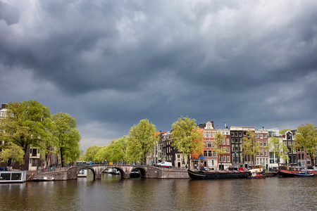 prinsengracht: City skyline of Amsterdam in Holland, Netherlands, traditional Dutch houses along Amstel River, bridge at Prinsengracht Canal, cityscape with stormy sky above.