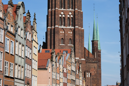 City of Gdansk in Poland, historical tenement houses, apartment buildings with gables against massive brick structure of the St. Marys Church in the Old Town