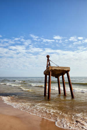 concrete structure: Abandoned crane at Baltic Sea shore in Poland, concrete platform, old structure on rusty metal legs