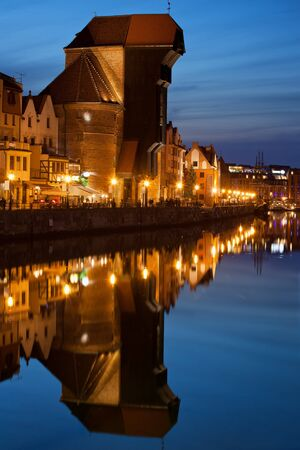 water town: The Crane at dusk in Old Town of Gdansk in Poland, medieval city landmark with water reflection on Motlawa River Stock Photo