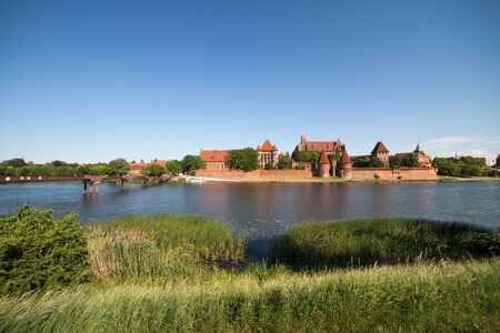 bullrush: View across Nogat River at Malbork Castle in Poland