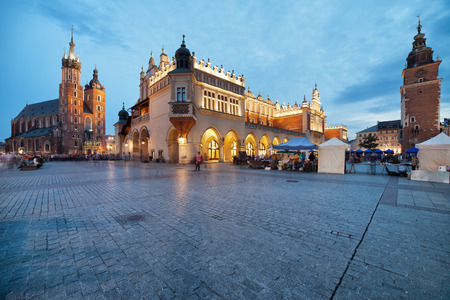 Old Town of Krakow at dusk in Poland, Main Market Square, on the left St. Mary Church (Bazylika Mariacka) Cloth Hall (Sukiennice) in the middle, Town Hall Tower on the right