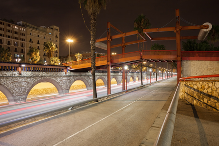 Spain, Barcelona, Ronda Litoral freeway at night with footbridge, arches of Passeig de Colom avenue, city infrastructure Stock Photo