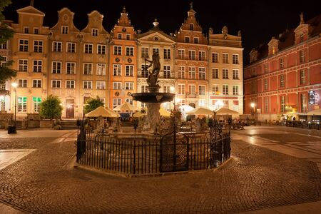 City of Gdansk by night in Poland, Old Town, Long Market street with Neptune Fountain, historic tenement houses with gables