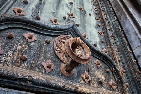 Ancient metal knocker on wrought iron reinforced old wooden doors to Girona Cathedral, Spain Stock Photo