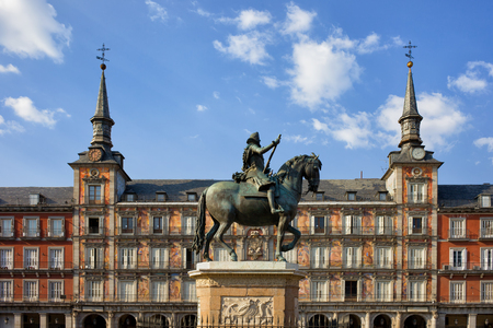 Plaza Mayor in city of Madrid in Spain, painted facade of Casa de la Panaderia and statue of King Philip III from 1616