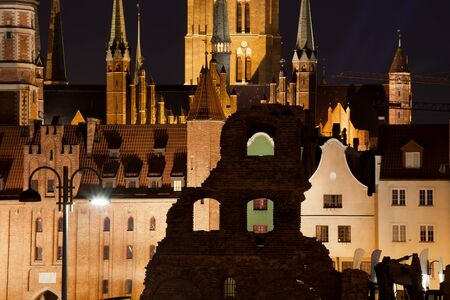 Old Town at night in city of Gdansk, Poland, historic architecture of St. Marys Church and Gate, gabled burgher houses and old granary remains.