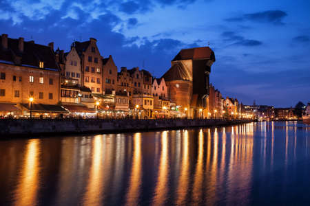 Old Town of Gdansk skyline at night in Poland, historic merchant houses, The Crane, city lights reflection on Motlawa River Stock Photo
