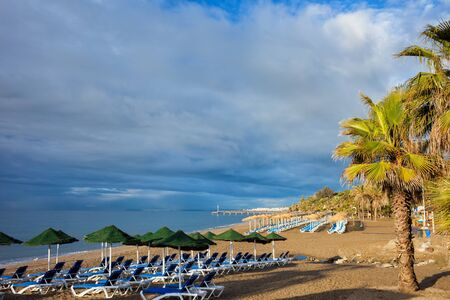 Beach in Marbella, resort city on Costa del Sol in Andalusia, Spain, sun loungers with umbrellas by the Mediterranean Sea in the morning