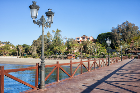 Spain, Marbella, pier with cast iron lamps and beach in resort city on Costa del Sol at Mediterranean Sea. Stock Photo