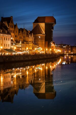 water town: Old Town of Gdansk in Poland by night, the Crane medieval landmark and symbol of an old port city with water reflection on Motlawa River