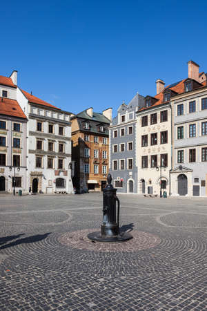 water town: Poland, Warsaw, Old Town Square, city landmark, historic houses and vintage water pump on cobbled plaza