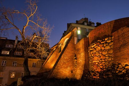 City wall fortification illuminated at night in Old Town of Warsaw, Poland, brick and stone structure with buttress