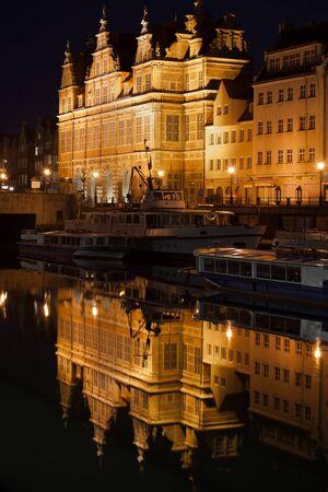 The Green Gate (Polish: Zielona Brama) illuminated at night in Gdansk, Poland, city landmark, Flemish mannerism architecture, reflection on Motlawa River