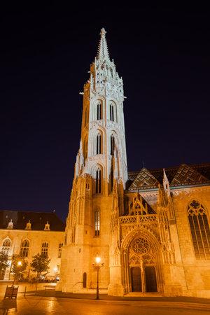Matthias Church in Budapest illuminated at night, historic city landmark in late Gothic style.