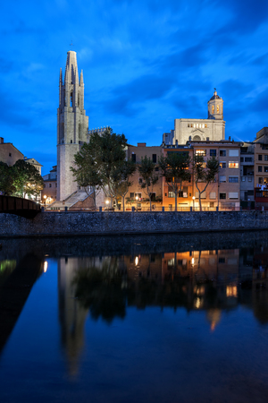 City of Girona Old Town skyline at dusk with Basilica of Sant Feliu, historic houses and Cathedral at Onyar River, Catalonia, Spain