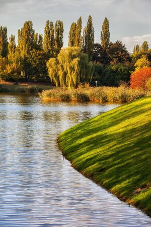 Grassy slope to the lake and early autumn foliage in Szczesliwicki Park in Warsaw city, Poland
