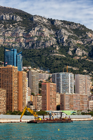 Monaco principality from the sea, barge with crane strengthens embankment breakwater, apartment towers, blocks of flats against a mountain Banco de Imagens