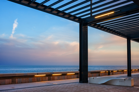 Sea promenade at dusk with pergola and bench in Monaco, southern Europe 스톡 콘텐츠