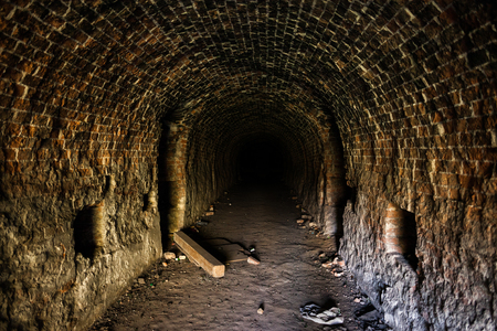 Grunge, spooky arched corridor in an abandoned brick building, urban exploration, haunted tunnel scary looking place. Banco de Imagens