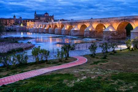 Spain, Cordoba, Roman Bridge (Puente Romano) on Guadalquivir River and Mosque Cathedral at twilight Фото со стока - 114904314