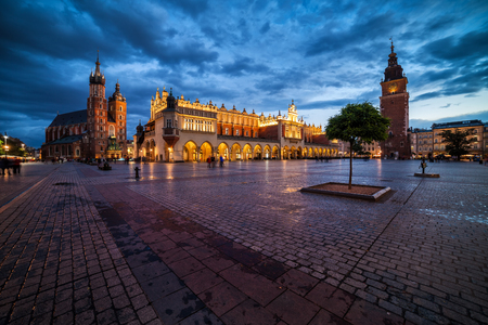 City of Krakow at dusk in Poland, Main Square in the Old Town, skyline with St. Mary Church, Cloth Hall (Sukiennice) and Town Hall Tower.