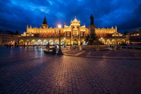 Krakow Main Square in the Old Town at night in Poland, illuminated Renaissance Cloth Hall (Sukiennice) and Adam Mickiewicz Monument. Stok Fotoğraf