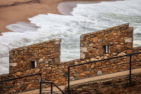 Defensive medieval stone wall battlement with two merlons and embrasures by the sea, old city wall fortification in Tossa de Mar, Catalonia, Spain 版權商用圖片
