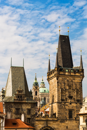 Lesser Town Bridge Towers in Prague, Czechia, taller tower in Late Gothic style architecture, smaller in Romanesque and Renaissance.
