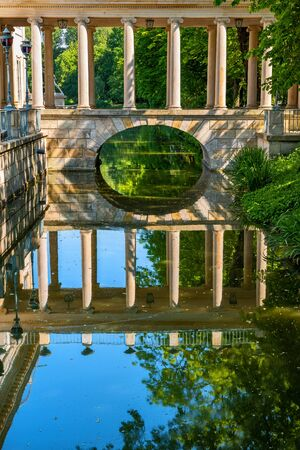 Lazienki Park in Warsaw, Poland, classical arch bridge with colonnade from 18th century over canal with water reflection, columned gallery in old Royal Baths Park.