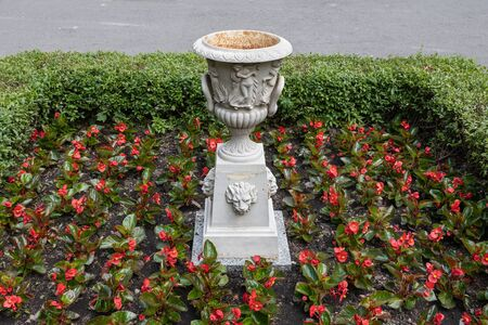 Pedestal for flowers, plants with classic style ornate vase in red flowers flowerbed with hedge, Saxon Garden, public park in Warsaw, Poland. Banque d'images - 125460280