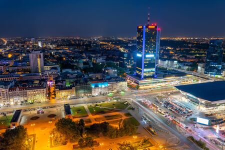 Warsaw cityscape in Poland, aerial view at night of the Polish capital city centre, central railway station on the right.