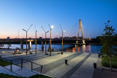Vistula River Boulevard with Swietokrzyski Bridge at dusk in city of Warsaw in Poland. 免版税图像