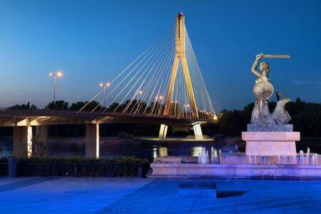 Das Meerjungfrau-Denkmal und die Swietokrzyski-Brücke an der Weichsel bei Nacht in Warschau in Polen. Standard-Bild