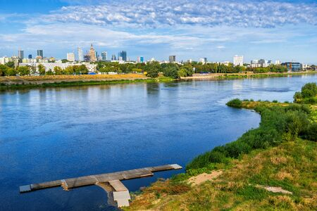Vistula river and city skyline of Warsaw in Poland, small wooden pier on the wild shore.