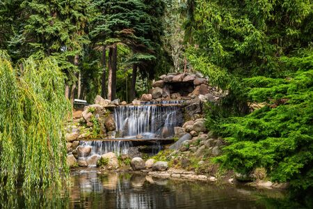 Landscape with cascading waterfall in scenic Skaryszewski Park in Warsaw, Poland.