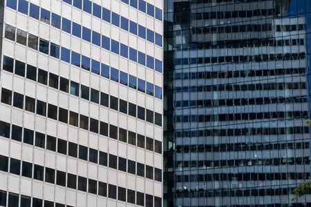Abstract modern architecture background of two contrasting corporate office skyscraper buildings with reflection in windows in the financial district. Stock Photo
