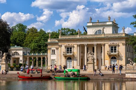 Warsaw, Poland - August 9, 2019: People sightseeing at Palace on the Isle in Royal Lazienki Park, Neoclassical  style city landmark