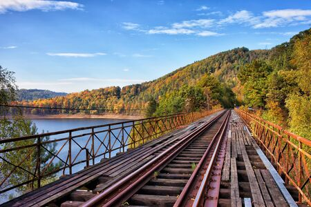 Old steel truss railway bridge over the Pilchowickie Lake in Poland. Lower Silesia region picturesque autumn countryside.