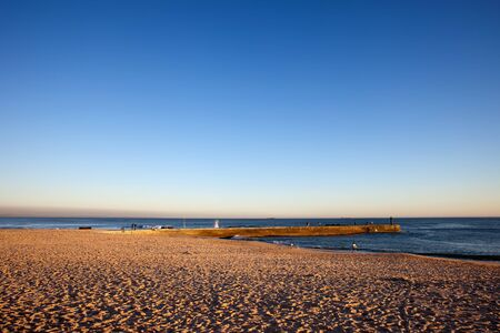 Sunset at the Tamariz beach in Estoril town by the the Atlantic Ocean in Portugal.